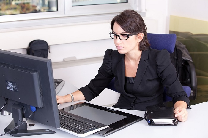 woman at desk on her computer