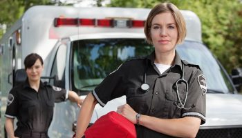 two EMTs standing in front of an ambulance