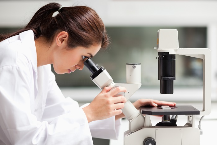 woman in lab coat using a microscope