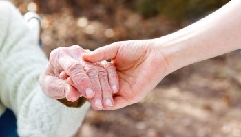 caregiver holding hands with old lady