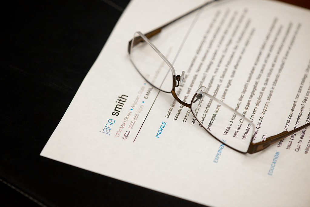 reading glasses on top of a resume